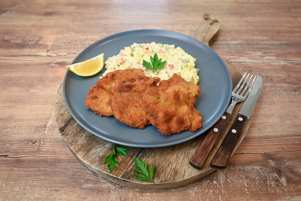 Pork schnitzel served with potato mayonnaise salad as the side.