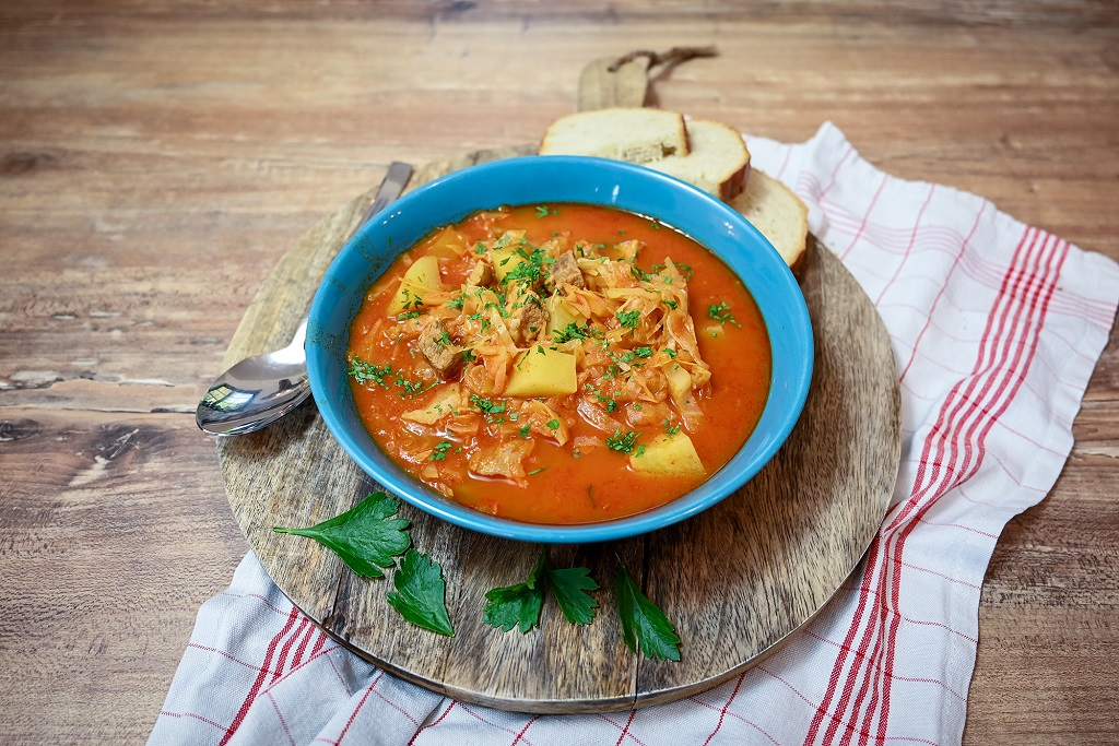 Serve this tomato soup with cabbage in a bowl, garnished with some parsley.