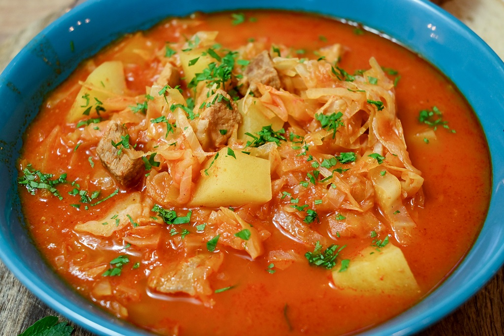 Tomato soup with cabbage, potatoes and pork shoulder.