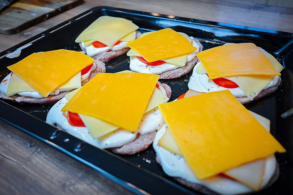 These pork chops are finished with two slices of cheese per piece.
