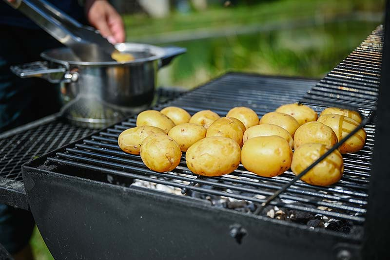 Start by grilling the potatoes.