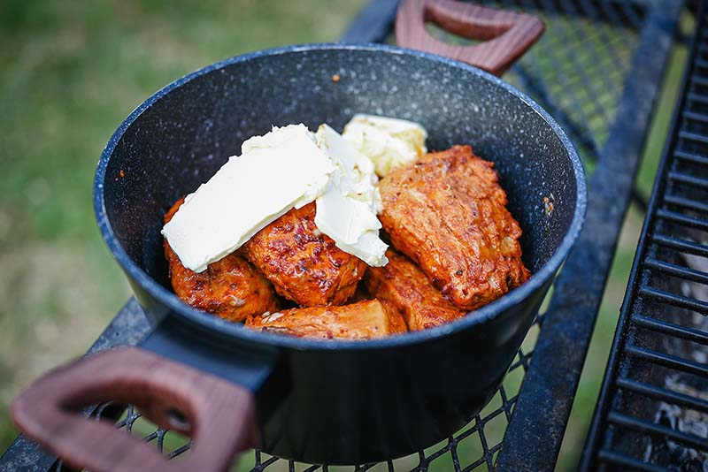Place the grilled steaks into a pot and add some butter.