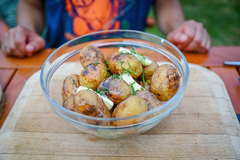 Add butter and herbs into the bowl with grilled potatoes.